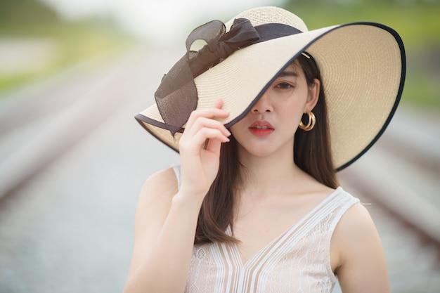 スタイリッシュなトレンディな白い帽子を身に着けている美しい少女の肖像画間近で屋外。帽子で隠された目