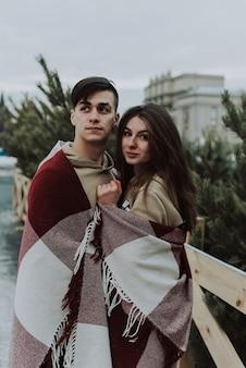 Открытый крупным планом портрет молодой красивой счастливой улыбающейся пары, завернутой в клетчатое одеяло. рождество, новый год, зимние каникулы.