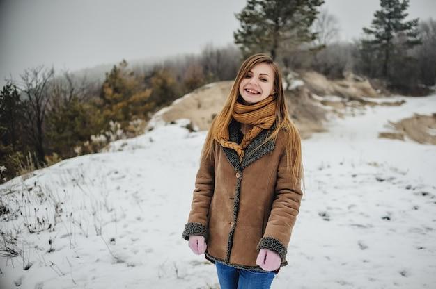 森の中でスカーフと手袋を着用して若い美しい幸せな笑顔の女の子の屋外クローズアップの肖像画。雪に覆われた公園でポーズをとるモデル。冬の休日のコンセプト。霜の降りる冬の散歩シーズン。