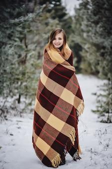 Открытый конец вверх по портрету молодой красивой счастливой улыбающейся девушки с одеялом в лесу. модель позирует в заснеженном парке. концепция зимних праздников. морозный сезон зимних прогулок.