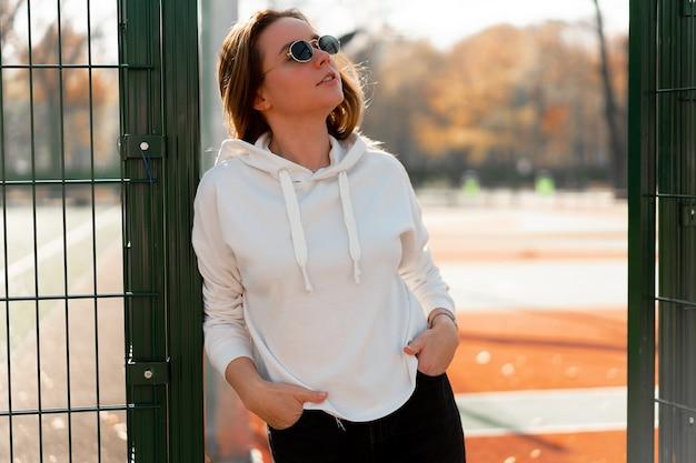 スポーツグラウンドの近くで、白いパーカーのセーターを着たサングラスをかけた長い髪の若い美しい女性の屋外クローズアップの肖像画。