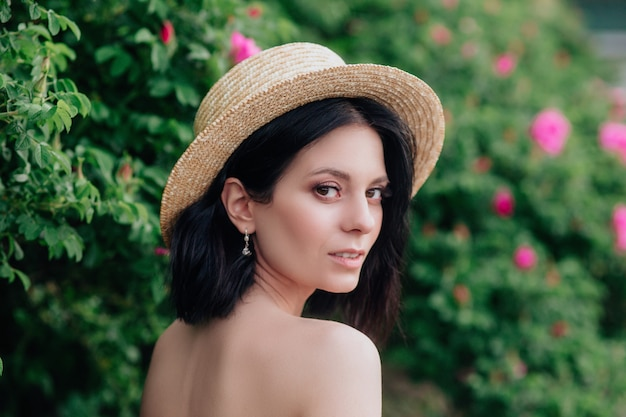 Outdoor close up portrait of young beautiful happy smiling woman wearing stylish straw hat.