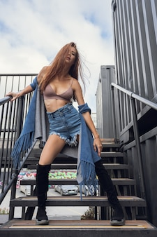 Outdoor close-up portrait of a young beautiful woman in a  shorts and top posing on the stairs against the backdrop of an industrial  container. autumn walking concept.