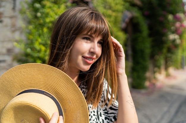 古いヨーロッパの都市で歩いている美しい女性の屋外クローズアップ夏の肖像画。麦わら帽子をかぶっています。