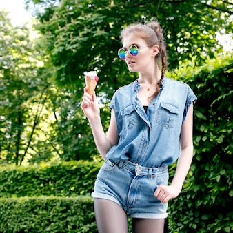 Outdoor closeup fashion portrait of young hipster crazy girl eating ice cream in summer hot weather