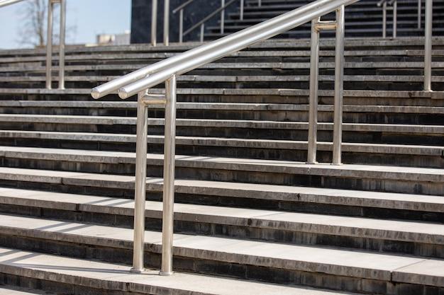스테인리스 손잡이가 있는 옥외 콘크리트 계단, 정면도, 클로즈업