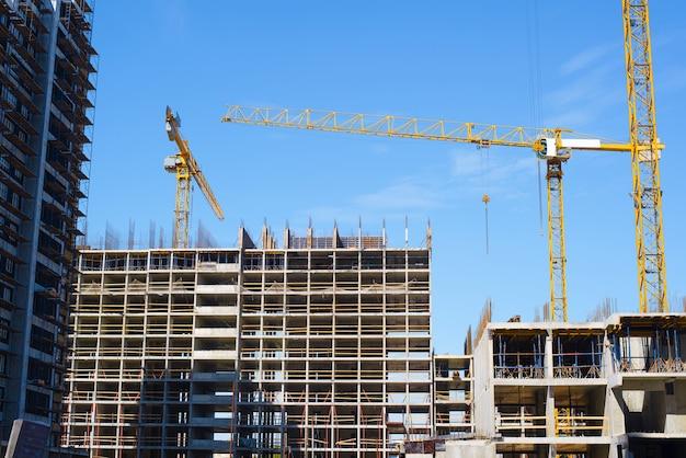 Открытая строительная площадка. краны и бетонная конструкция строящегося здания. многоэтажные дома. строительная техника