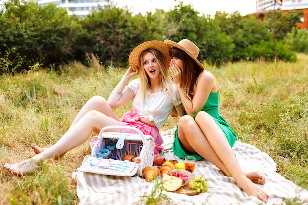 Outdoor countryside portrait of two happy best friends enjoying picnic