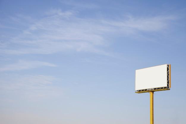An outdoor empty advertising billboard against blue sky