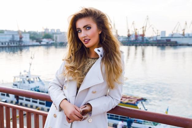 白いカシミアの白いコートを着て夢と考え、清楚な海のポートをポーズするセクシーなエレガントな女性の屋外の秋のファッションの肖像画は、髪をカールし、明るい化粧をしています。夕陽、柔らかな色。