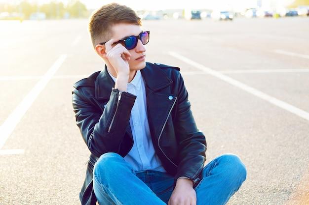市の駐車場でポーズをとって、デニムジーンズのバイカーの黒革のジャケットとサングラスを着てスタイリッシュな男の屋外秋ファッションポートレート。