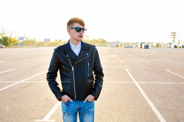 Outdoor fall fashion portrait of stylish man posing at city parking, wearing denim jeans biker black leather jacket and sunglasses.