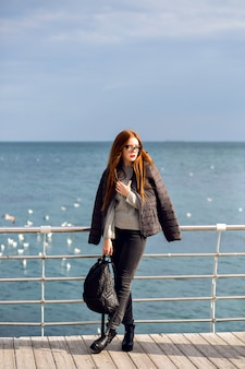 Outdoor fall lifestyle portrait of stylish woman walking alone at the beach, amazing view on the sea, travel alone, street fashion.