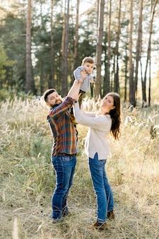 행복 한 젊은 부모의 야외 가족 초상화, 세련된 캐주얼 옷을 입고, 재미와 화창한 날에 가을 숲에서 산책하는 동안 그들의 작은 귀여운 아기 아들을 들어 올려
