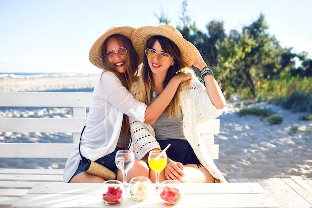 Открытый фанни портрет двух сестер избивает друзей. девушка весело обнимает, улыбается и делает гримасы в баре на пляже, в хипстерской одежде в стиле бохо, пьет вкусные коктейли, летние каникулы на океане.