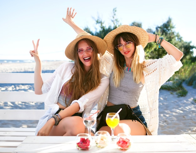 Outdoor  fanny portrait of two sister beat  friends girl having fun hugs smiling and making grimaces on beach bar, boho hipster clothes, drinking tasty cocktails, summer ocean vacation .