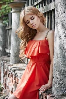 Фото молодой женщины внешней моды красивая около старого лета усадьбы. портрет девушки блондинки в красном платье