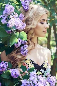 야외 패션 여름 라일락 꽃으로 둘러싸인 아름다운 젊은 여성. 봄꽃 라일락 덤불. 여자 금발의 초상화