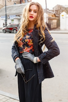 Outdoor fashion image of beautiful elegant woman with long curly blonde hairs and big bright full lips posing at the street wearing elegant warm coat. autumn portrait.