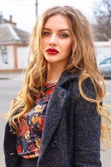 長い巻き毛のブロンドの髪とエレガントな暖かいコートを着ている通りでポーズをとって大きな明るい完全な唇を持つ美しいエレガントな女性のアウトドアファッションのイメージ。秋のポートレート。