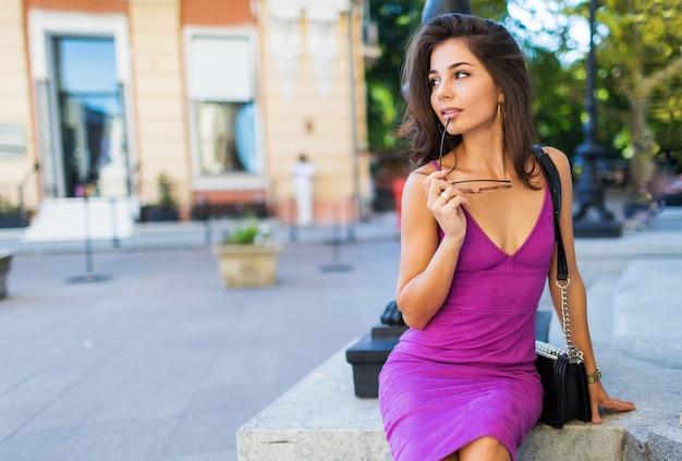 誰かを待っていると夢を見て、路上で自由な時間を楽しんでいるスタイリッシュなベルベットのドレスでかなり優雅な女性のアウトドアファッションのイメージ。暖かい日当たりの良い色。ブルネットのウェーブのかかった髪型。