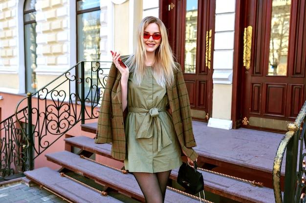 パリの通りでポーズをとる見事な金髪モデルの女性、特大のモダンなジャケット、秋の春半ばシーズン、暖かいトーンの色でトレンディな服でポーズの屋外ファッション画像。