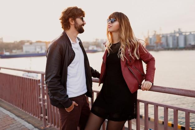 カジュアルな服装、革のジャケット、サングラスが橋の上に立っているスタイリッシュなカップルのアウトドアファッションのイメージ。ロマンチックな時間を一緒に過ごす彼のガールフレンドとひげを持つハンサムな男。