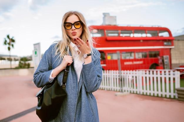 Внешний вид моды стильной молодой женщины, позирующей на лондонской улице, элегантной повседневной деловой одежде, отправляющей поцелуй и смотрящей в камеру, осенне-весеннее время в середине сезона, тонированные цвета.