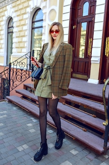 Outdoor fashion image of stunning blonde model woman posing on the paris street, trendy outfit with oversized modern jacket, autumn spring mid season, warm toned colors.
