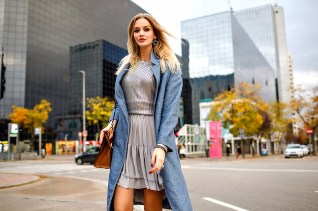 Outdoor fashion lifestyle portrait of blonde pretty young businesswoman, walking at modern buildings area, wearing blue coat and feminine grey dress.