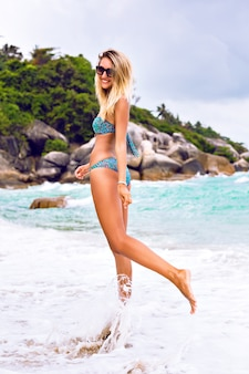 Outdoor fashion lifestyle portrait go young sexy blonde woman with fit tanned body, wearing stylish bikini and sunglasses, having fun on island tropical beach. jumping smiling and screaming.