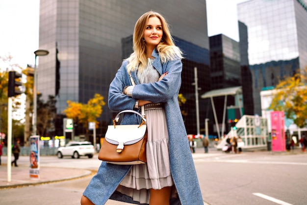 モダンな建物のエリアを歩いて、青いコートとフェミニンなグレーのドレスを着ている金髪のかなり若い実業家のアウトドアファッションライフスタイルの肖像画。