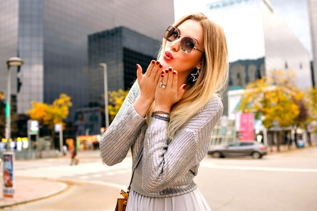 Outdoor fashion lifestyle portrait of pretty elegant blonde woman wearing trendy stylish feminine  outfit  and leather bag, posing near modern business center in new york, freedom travel time.