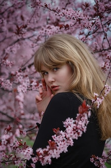 Outdoor fashion photo of a beautiful young lady in a pink cherry blossom garden. like a sakura in japan.