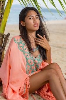 Ritratto di moda all'aperto di donna asiatica sulla spiaggia tropicale, sta rilassando, sognando. indossare gioielli, bracciale e collana.