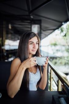 Ritratto di moda all'aperto di bella ragazza che beve tè e caffè