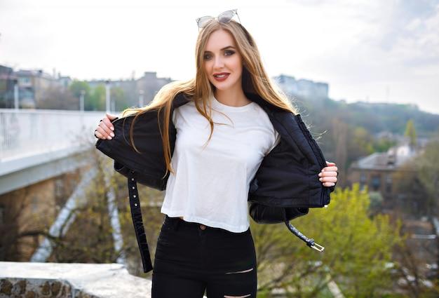 Ritratto di moda all'aperto di donna bionda carina sorridente e divertirsi, capelli lunghi, trucco luminoso, giacca di pelle da motociclista, moda di strada.