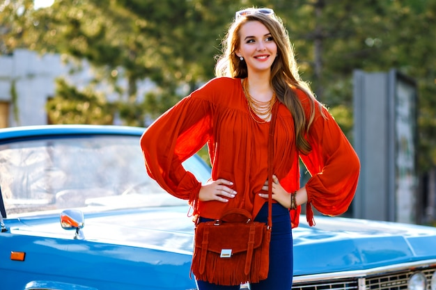 Outdoor fashion portrait of elegant young woman with amazing blonde long hairs and pretty face smiling and enjoy sunny day, posing near blue vintage car, modern glamour boho outfit, bad and jewelry.