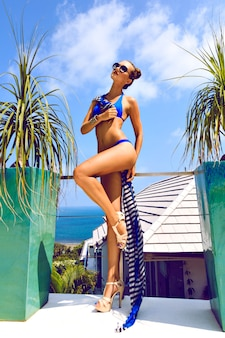 Outdoor fashion portrait of glamour lady enjoying her vacation on luxury villa in hot tropical island, wearing stylish sunglasses and navy bikini. perfect tanned body and long legs.