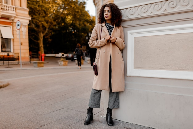 Outdoor fashion portrait of glamour sensual young stylish black lady wearing trendy fall outfit, grey velvet sweater and beige wool coat.