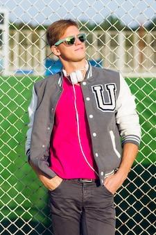 Ritratto di moda all'aperto del bel ragazzo in abito sportivo primavera elegante e in posa vicino al campo sportivo.