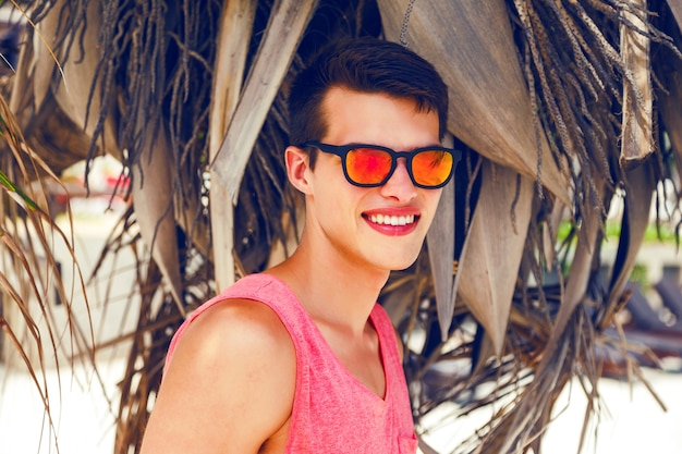 Outdoor fashion portrait of handsome stylish guy spending great time at tropical beach, posing near coconut palm, wearing bright outfit and neon sunglasses.
