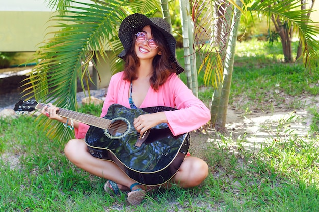 Outdoor fashion portrait of happy pretty smiling hippie woman sitting at the grass and holding acoustic guitar. hot tropical country, green background. summer outfit with hat and pink sunglasses.
