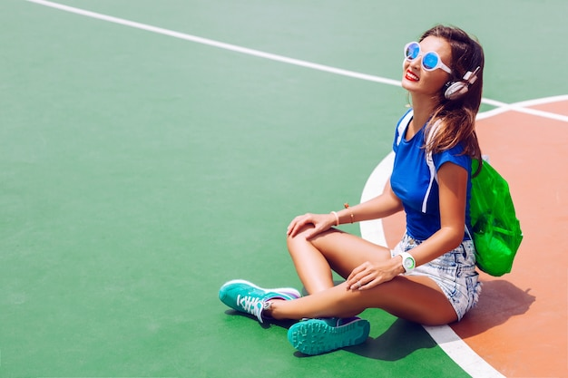 Outdoor fashion portrait of hipster girl posing at sports ground in bright summer outfit, listening music and wearing stylish sportive shoes backpack and sunglasses.