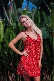 Outdoor fashion portrait natural beauty young pretty woman with light make up, star earings, bracelet and ring. female in red summer flower dress