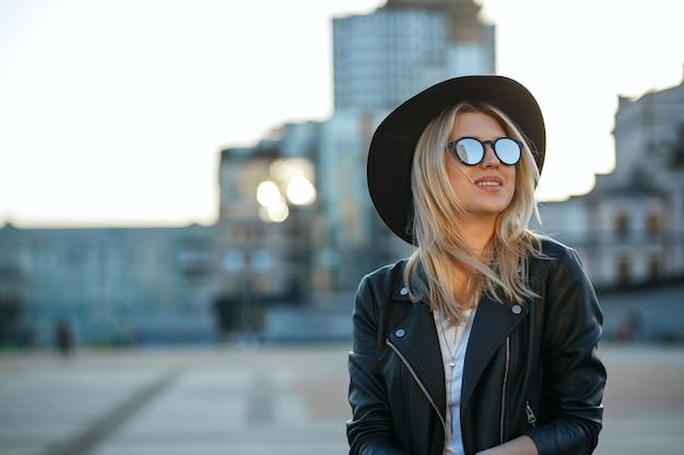 모자와 거울 선글라스를 쓴 쾌활한 금발 여성의 야외 패션 초상화. 텍스트를 위한 공간