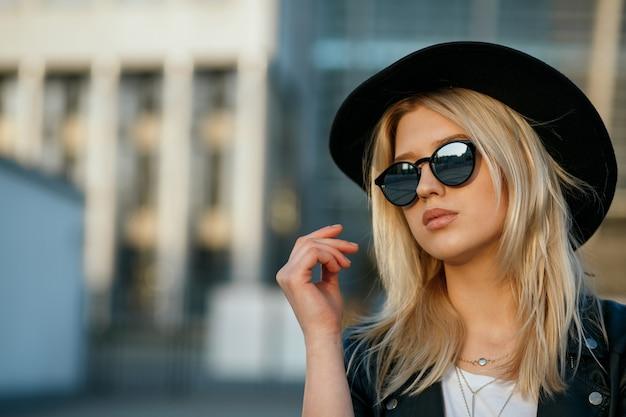 모자와 거울 선글라스를 쓴 멋진 금발 여성의 야외 패션 초상화. 텍스트를 위한 공간