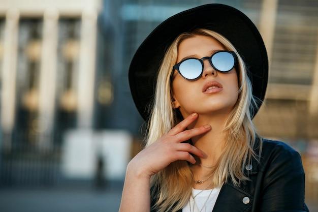 모자와 거울 선글라스를 쓴 매력적인 금발 여성의 야외 패션 초상화. 텍스트를 위한 공간