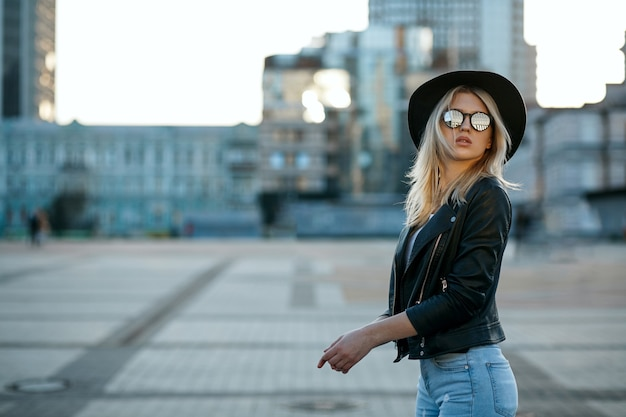 모자와 거울 안경을 쓴 고급스러운 금발 소녀의 야외 패션 초상화. 텍스트를 위한 공간