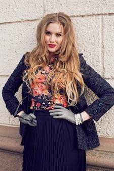 Открытый модный портрет красивой стильной девушки, позирующей на улице в элегантном стильном платье-пальто и туфлях, с длинными рыжими волосами и идеально подобранными аксессуарами.